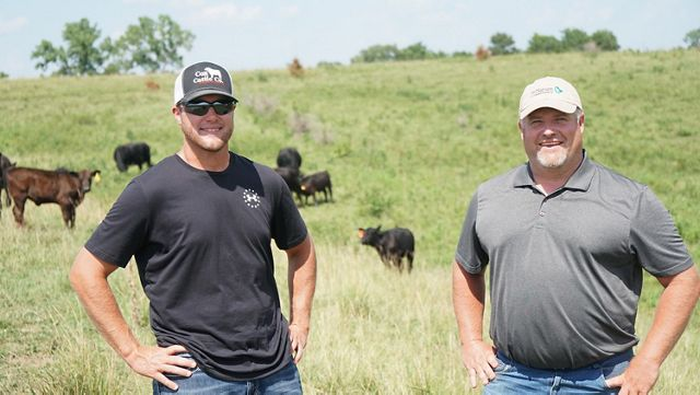 Two ranchers stand in a field with cows in background.