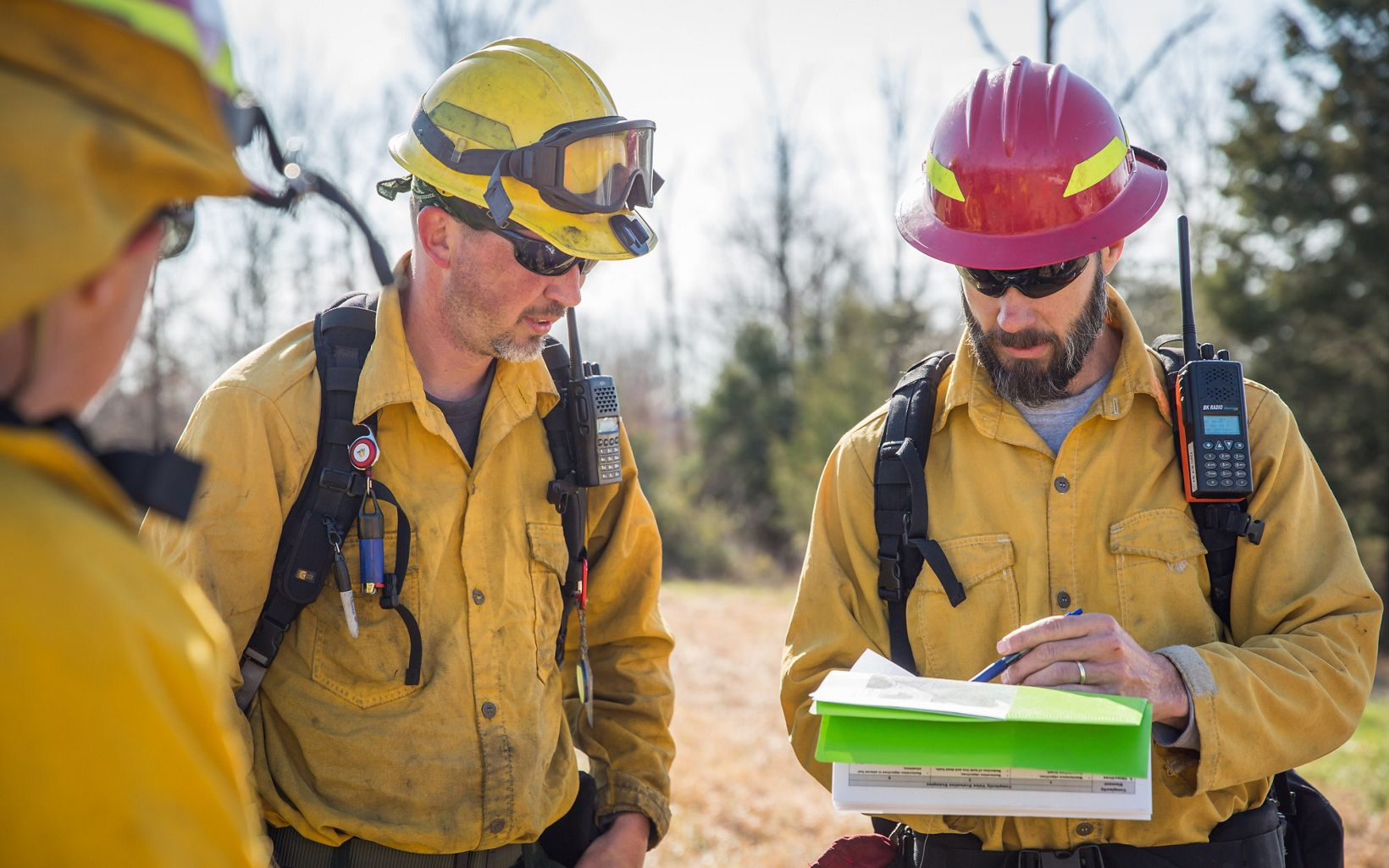 Three members of a fire crew consult a map.