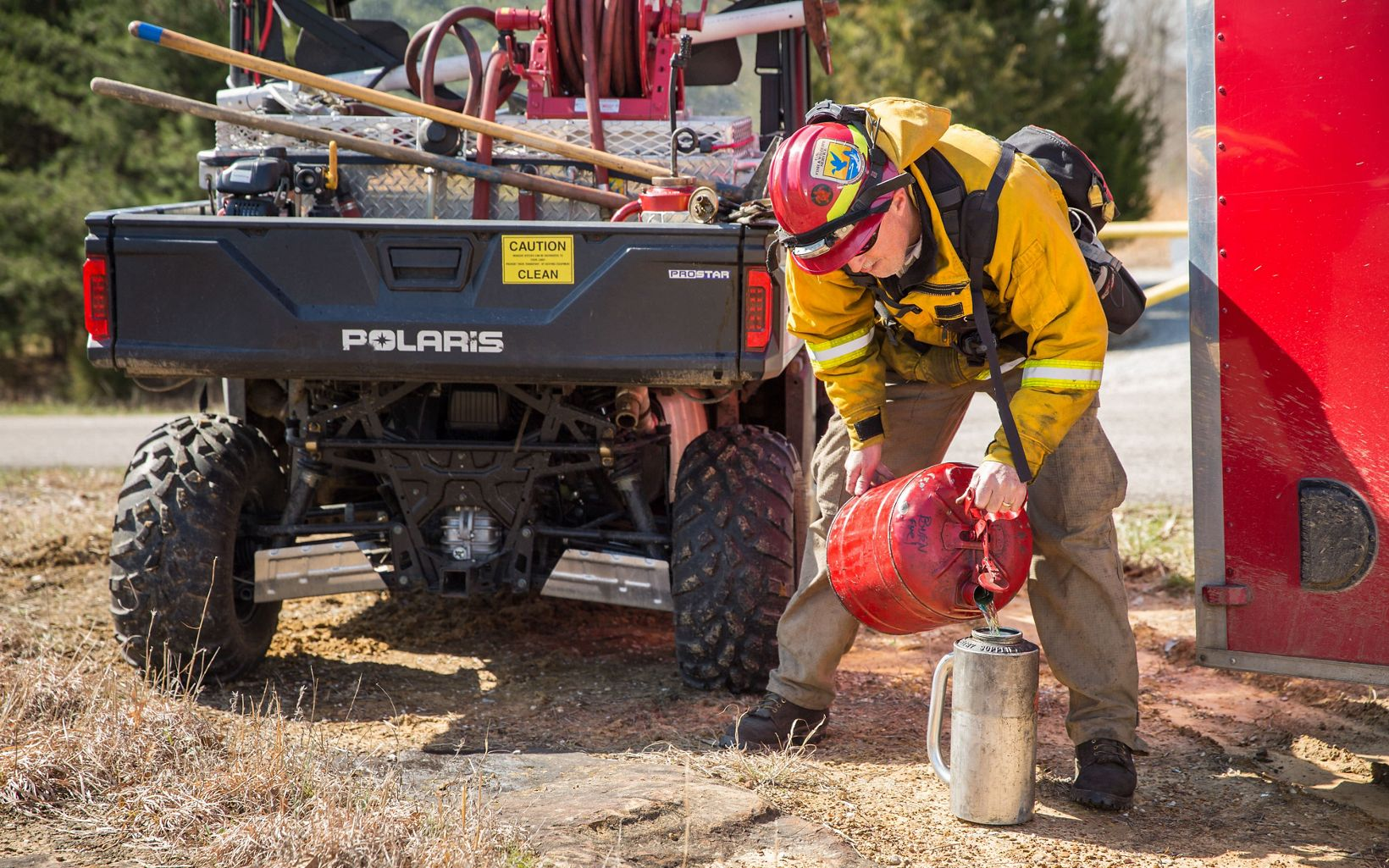 A fire crew member holds a red container.