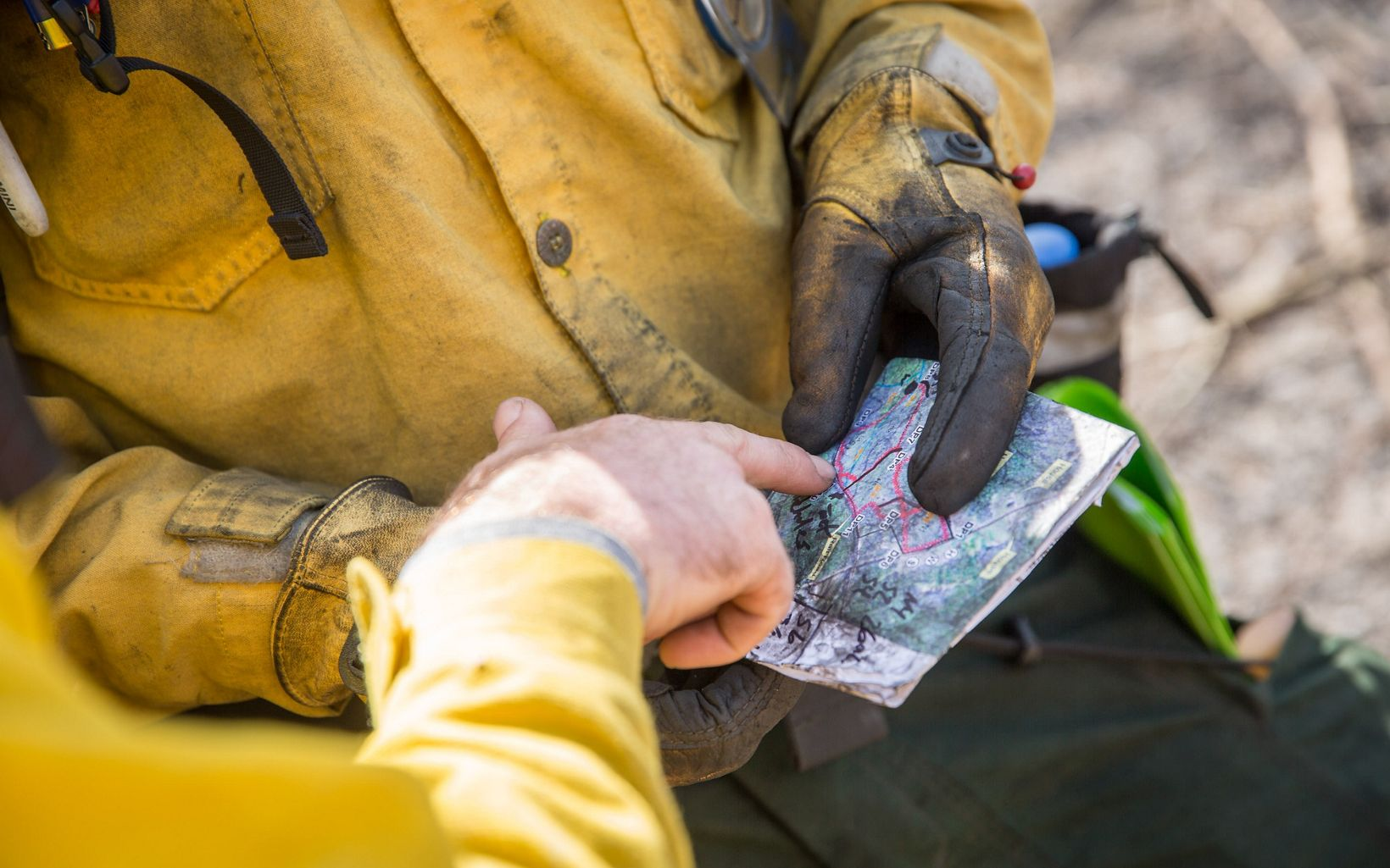 The hands of fire crew members hold a map.