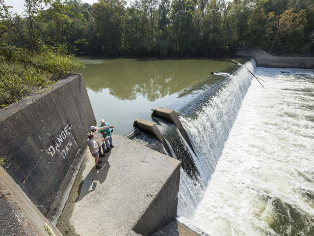 People standing at a large dam in a river.