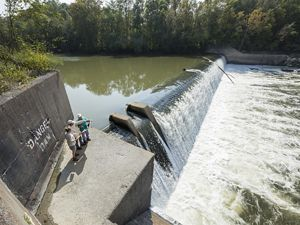 Three people stand at a large dam on a river.