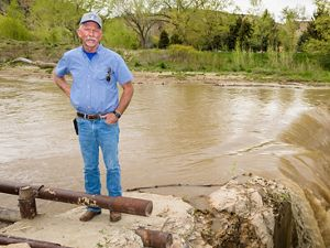 A farmer stands in front of a muddy canal as it spills over a small waterfall.
