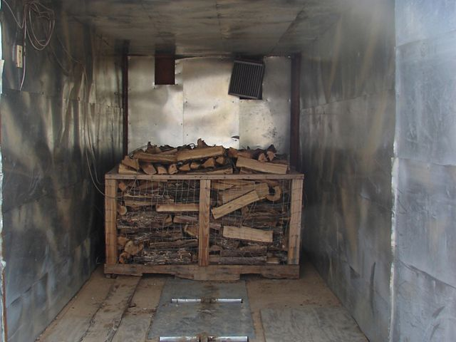Wood is piled up inside of a small metal space.