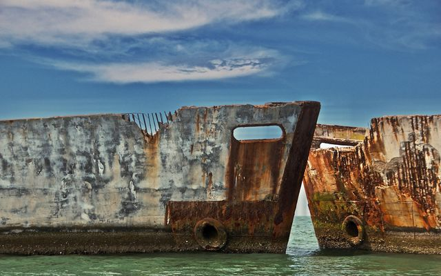 Two weather streaked concrete ship hulks sit nose to nose to create a breakwater protecting a calm, shallow recreation area.
