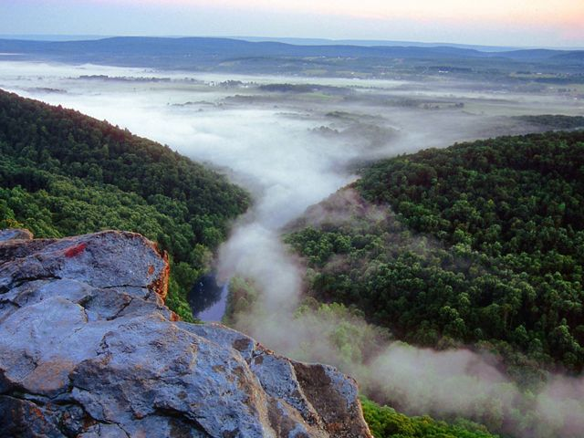 A mist emerges between two mountain ridges.