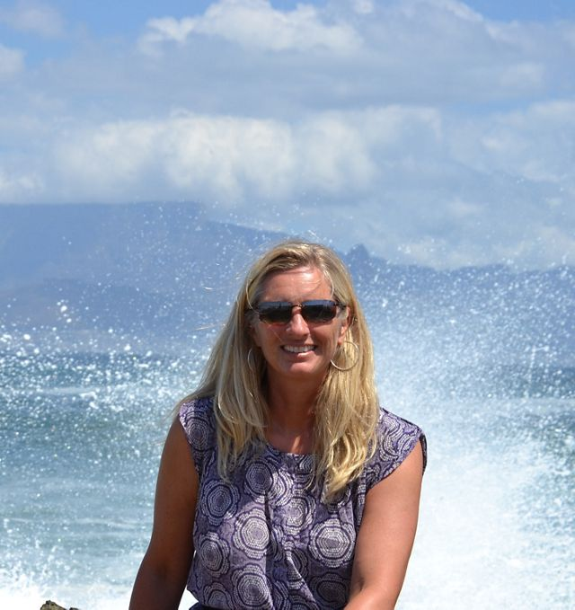 Hawaii Board of Trustee member Kris Billetter sits at the ocean, with waves crashing behind her.