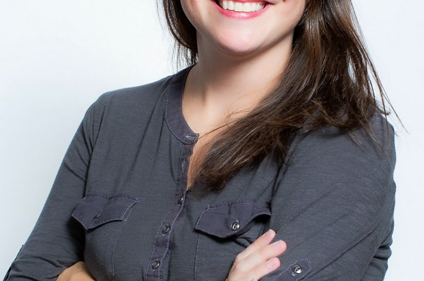 Headshot of MD/DC Director of Development Kristin Bramell. A smiling woman wearing a dark gray blouse poses in front of a white backdrop with her arms casually folded across her chest.