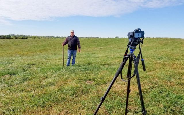 A man stands in an open field in front of a camera on a tripod.