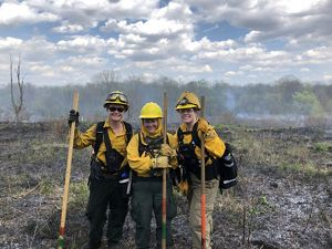Three of the women who helped lead a controlled burn art Ives Road Fen Preserve in Michigan.