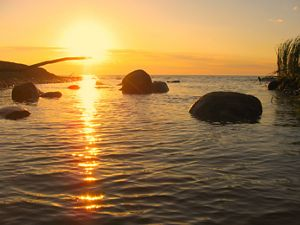 A sunset over Lake Michigan. Large rocks are in view peeking out from the water. The sky is orange casting a long light across the surface of the lake