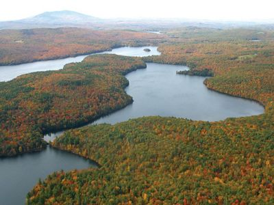 An aerial view of fall colors at a wooded peninsula between two lakes.