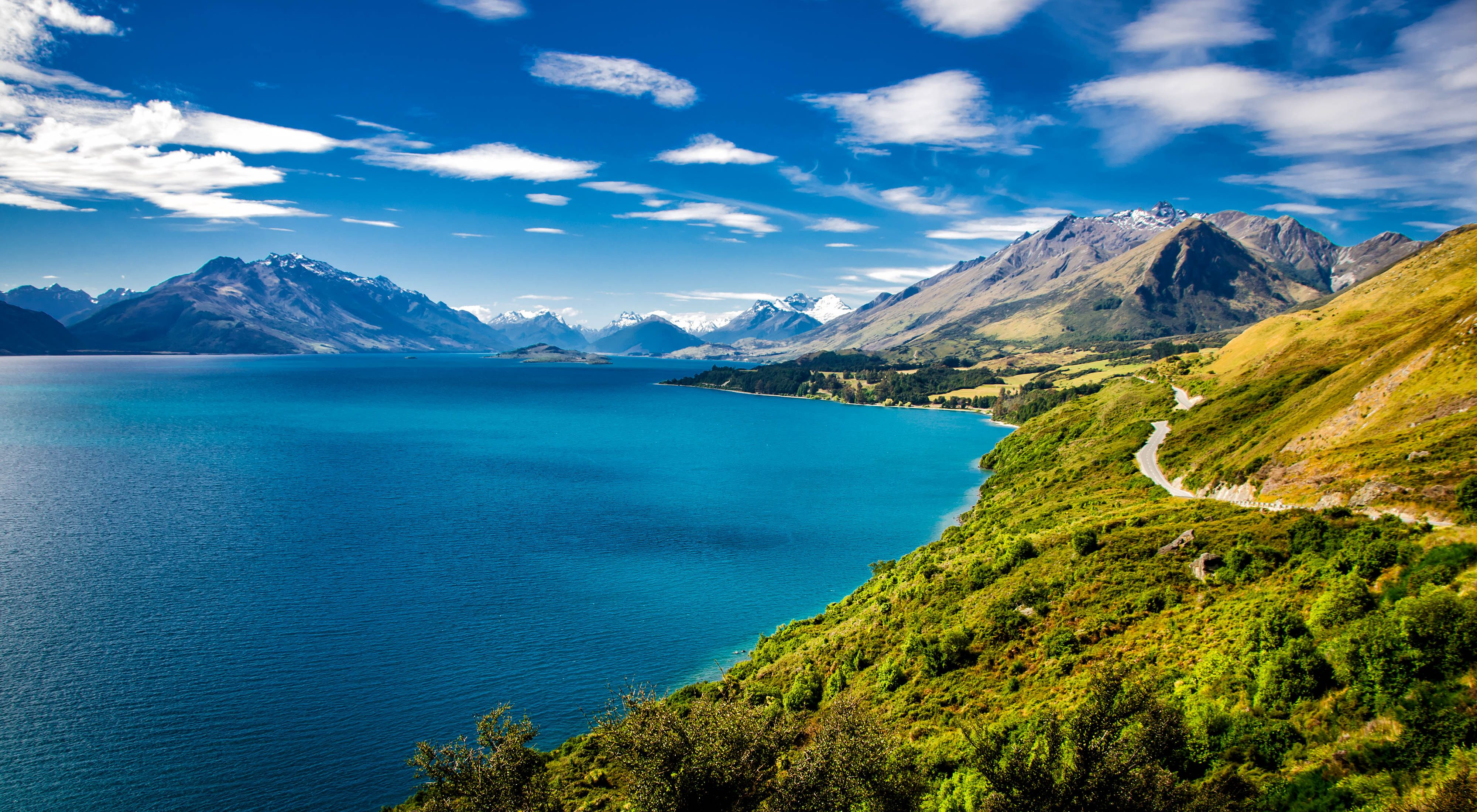 Summer view of Lake Wakatipu and the road from Queenstown to Glenorchy.  Southern Alps mountains in the distance.