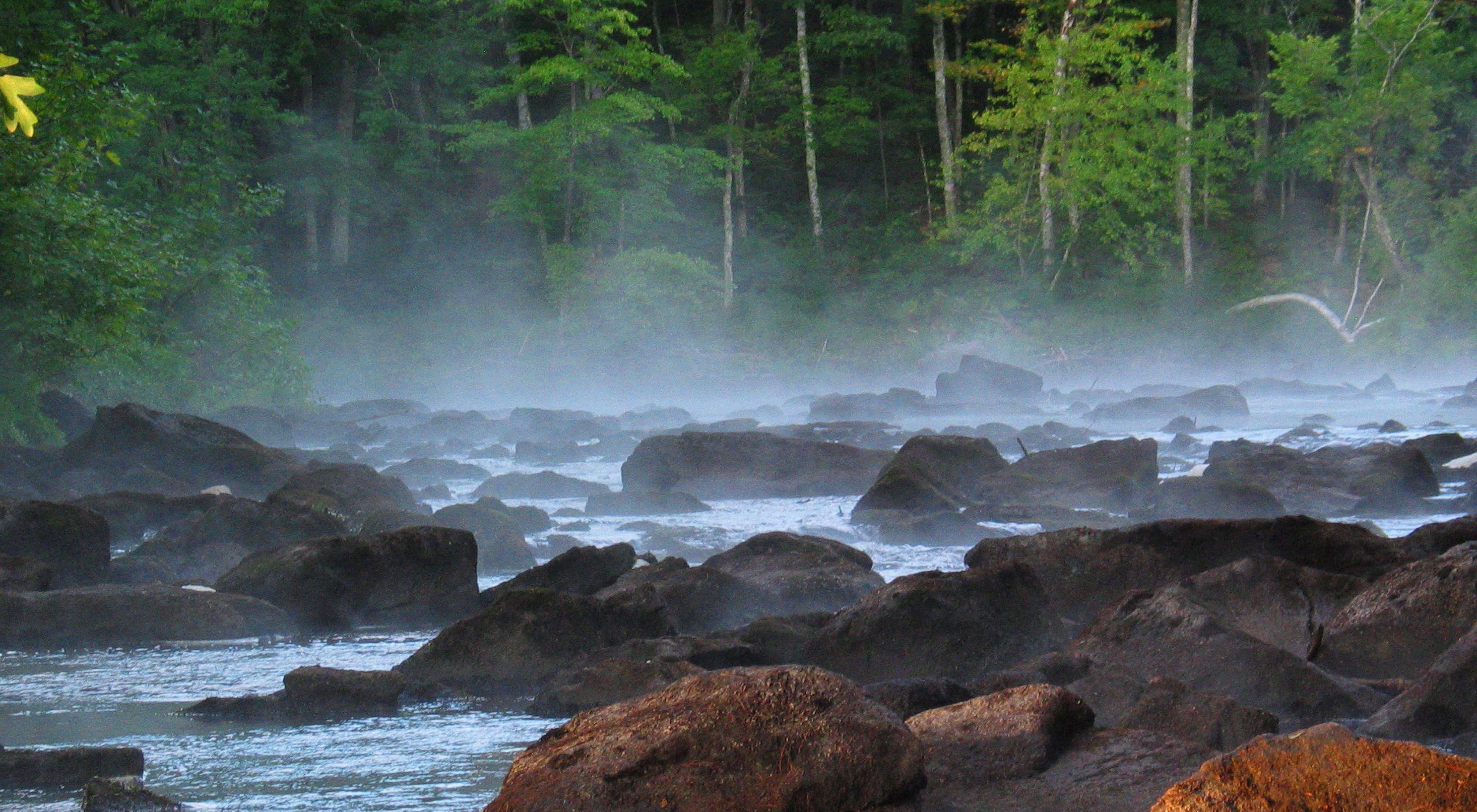 Fog arising from a rocky river.