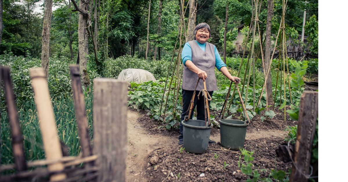 A villager carries buckets at a farm around Laohegou