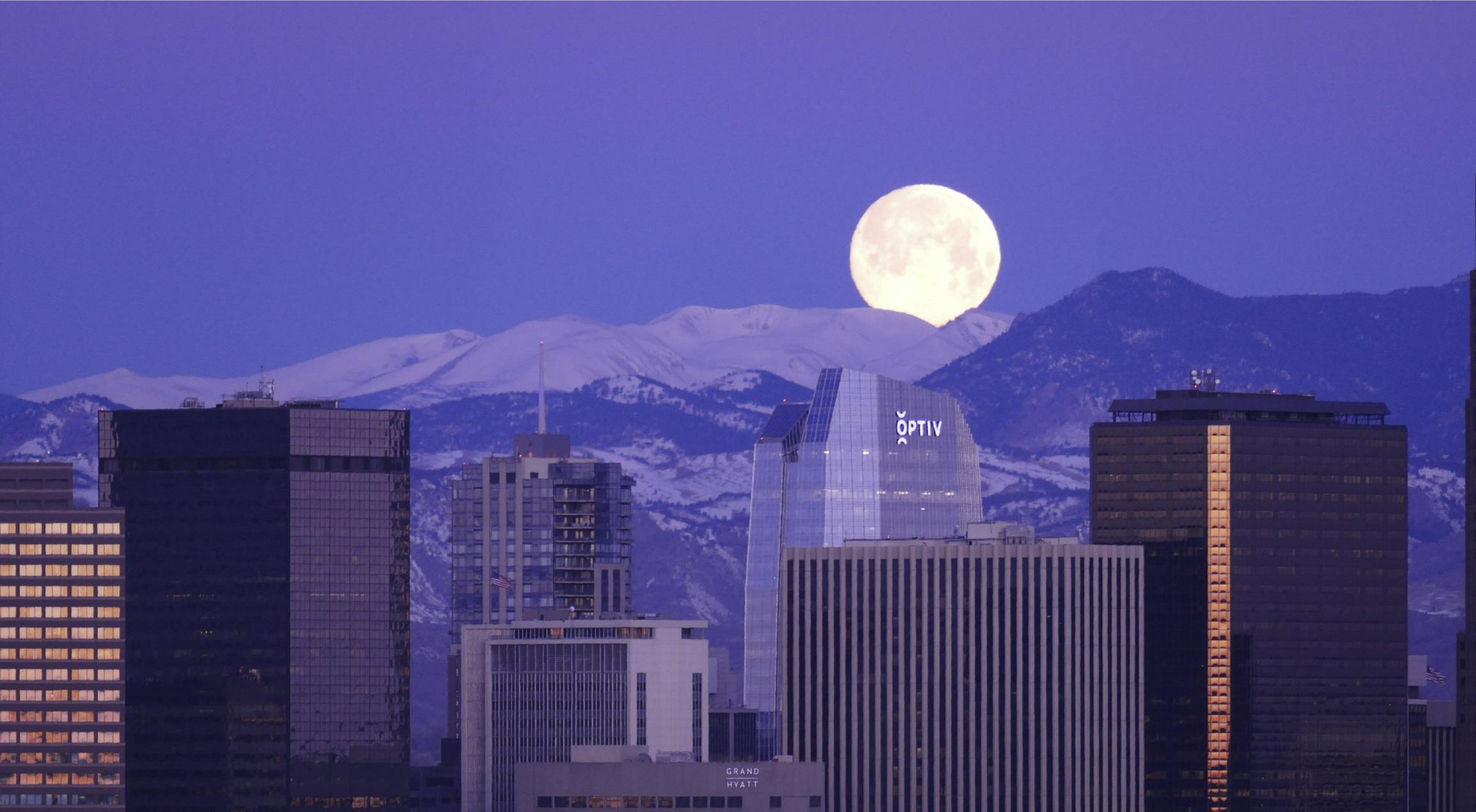 A huge moon rising over snow-capped mountains behind the Denver skyline.