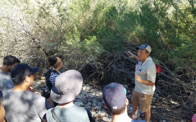 Leonard Warren explaining native species habitat to UNLV landscape architecture students and informing their designs during a field trip to Clark County Wetlands Park.