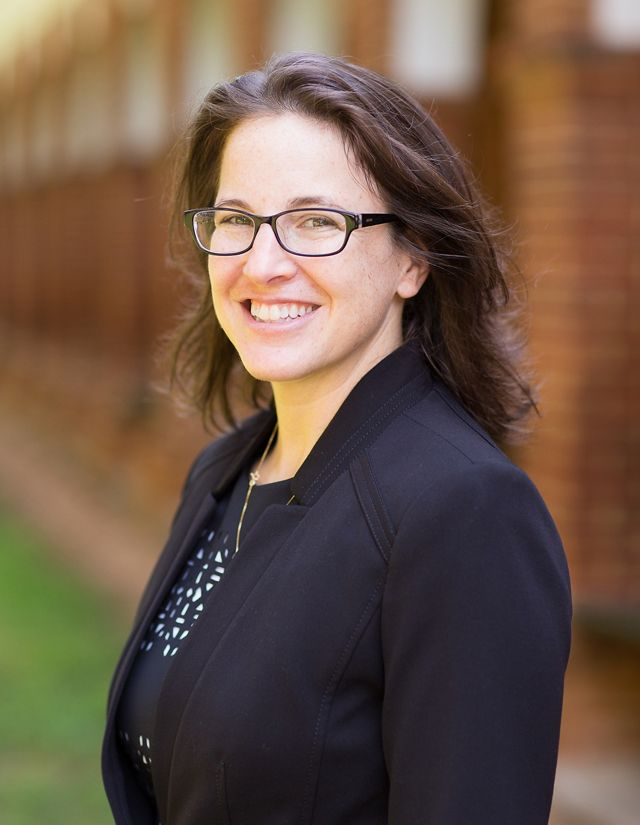 Headshot of Virginia Energy and Climate Policy Manager Lena Lewis. A smiling woman in a navy blue suit poses in front of a row of brick columns.