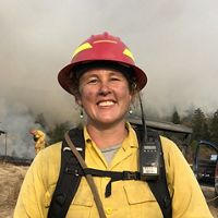 Women in yellow fire gear & red hardhat stands by prescribed burn.