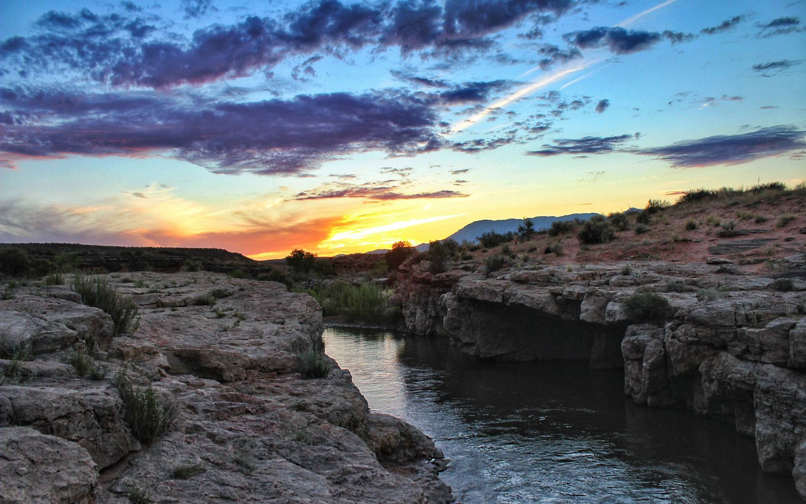 Scattered vegetationn on a desert landscape cut throuugh by the Virgin River and lit by the sun just beyond the horizon.