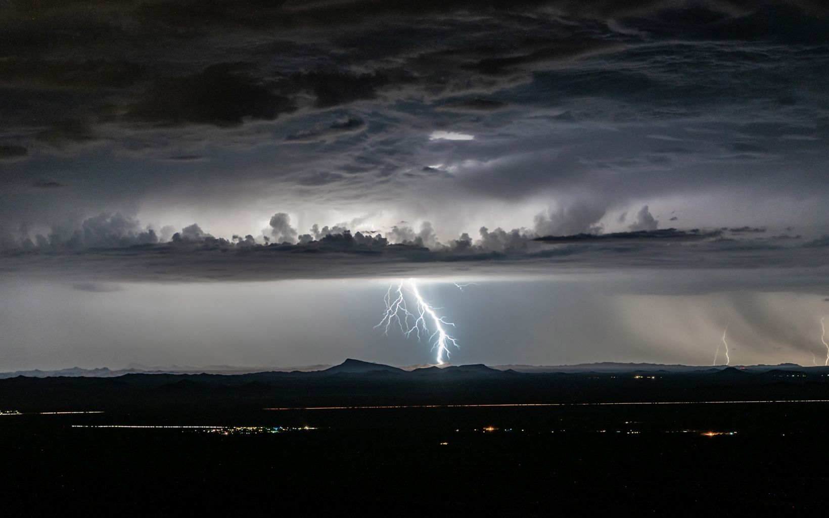 Black and white photo of bright lightning going from clouds to the ground in a dark sky.