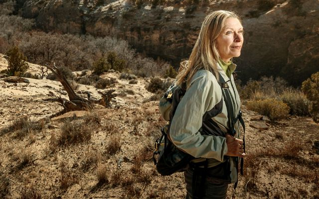 Linda Whitham stands on a sparsely vegetated, rocky hillside.