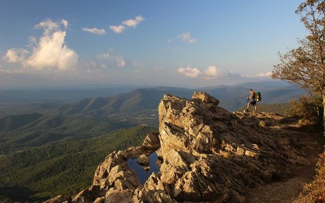 hiker with backpack and poles stands on rocky crag of a mountain overlooking a valley