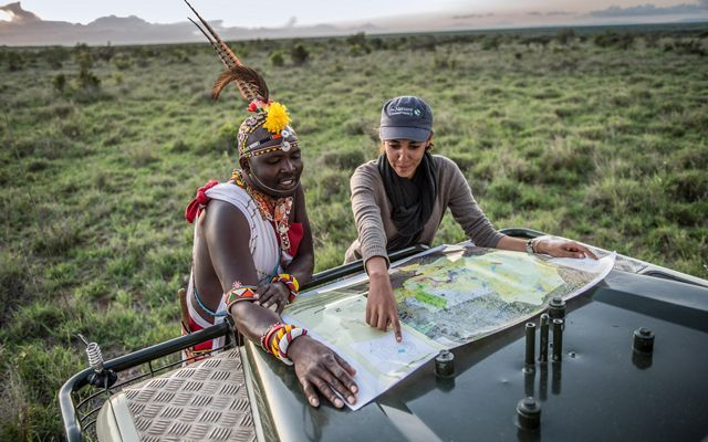 Ecotourism guide Sam Brown and TNC's Loisaba Project Manager Chantal Migongo-Bake review a map spread over the hood of a car in the Loisaba Conservancy in northern Kenya.