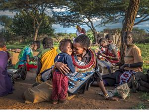 Ntipiyon Nonguta and son Bernard relax with their neighbors as they make beaded belts in Laikipia, northern Kenya. Their stunning designs are available worldwide.