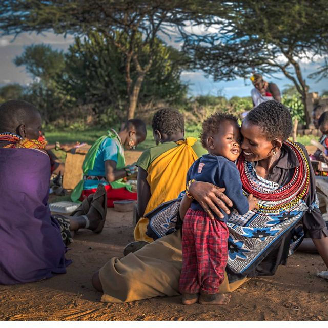 Ntipiyon Nonguta and her son Bernard relax with their neighbors as they make beaded belts for Loisaba Community Trust in northern Kenya to be sold to international markets.