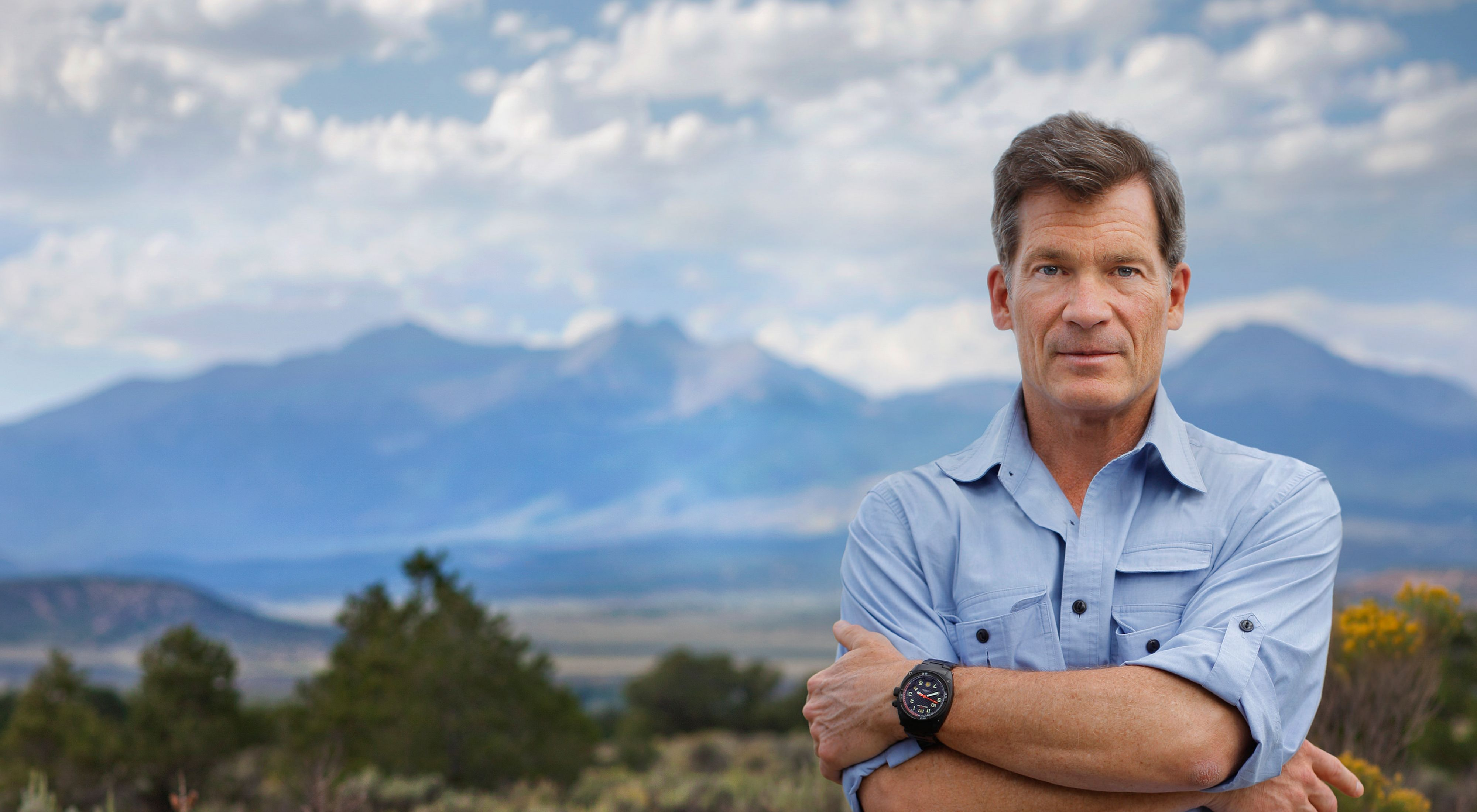Man in light blue shirt stands with arms folded in front of mountain range.