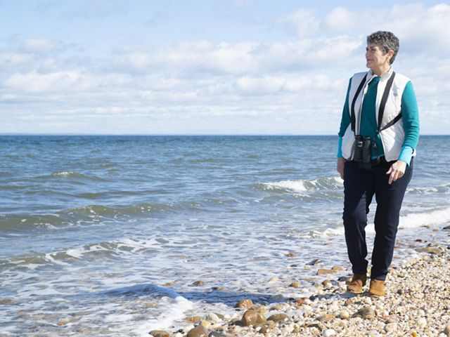 Louise Harrison walking on a shoreline at right looking left to the ocean shore.