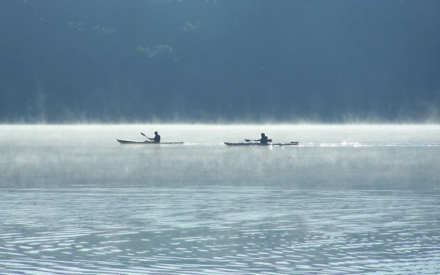 Mist rises from the waters of Lulu Lake as two kayakers paddle by.
