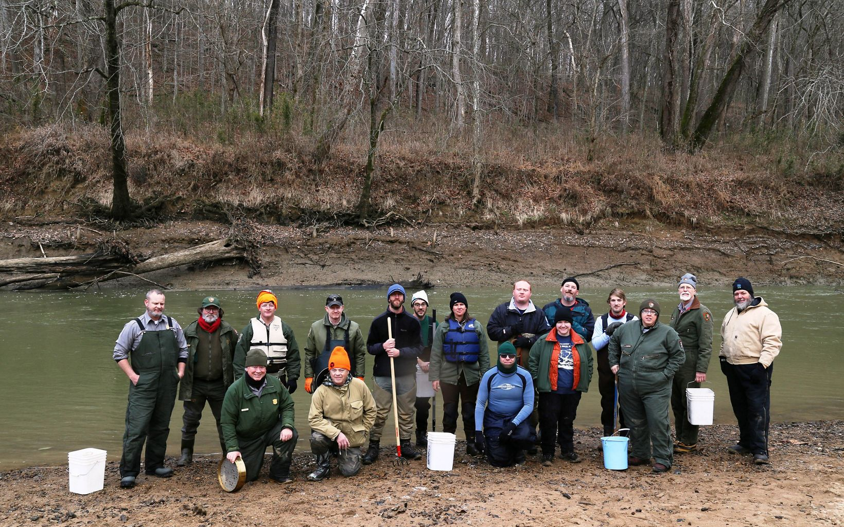 A group of volunteers poses with buckets and tools.