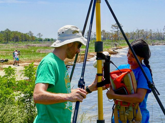 A man and woman set up monitoring equipment along the shoreline of an island in the Chesapeake Bay.