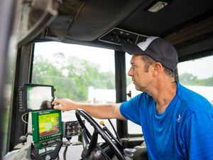 A man wearing a blue shirt and cap sits in the cab of a tractor. He adjusts the display units in front of him that help guide the application of fertilizer to his crops.