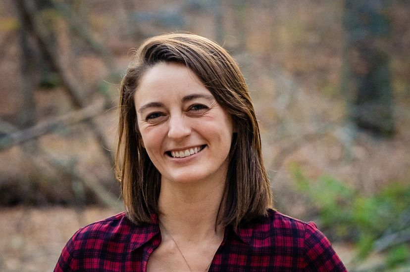 Casual headshot of Coastal Science Program Manager Jackie Specht. A smiling woman stands on a forest trail with blurred trees visible behind her.