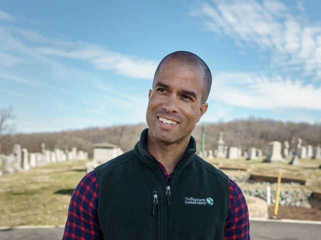 A smiling man wearing a black fleece stands in front of a TNC green infrastructure project under construction at a cemetery.