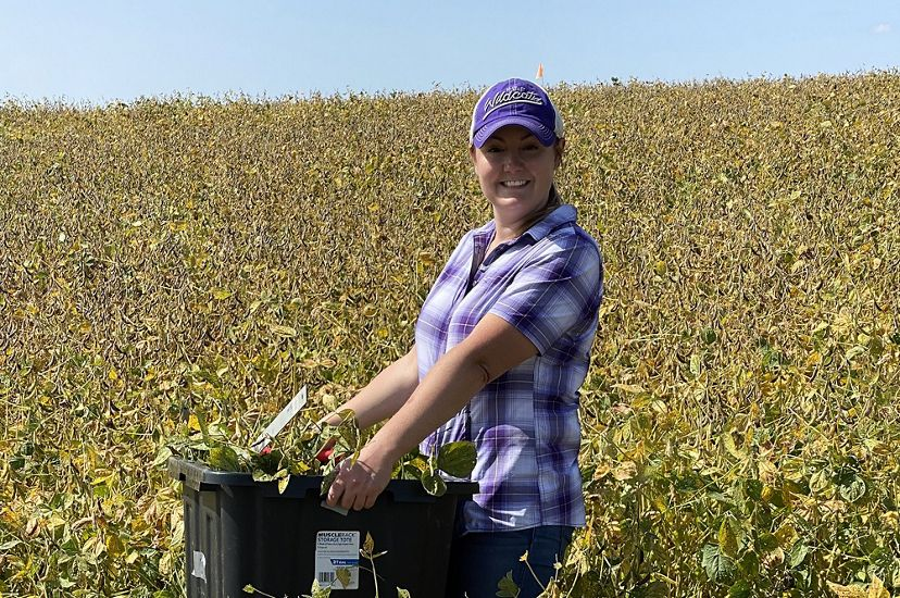 A smiling woman stands in a farm field holding a large rubber tote filled with plants. She is surrounded by hip-high green plants that stretch to the horizon behind her.