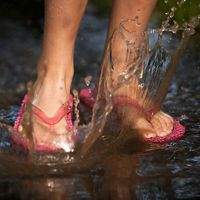 Child splashes their feet in a water puddle.
