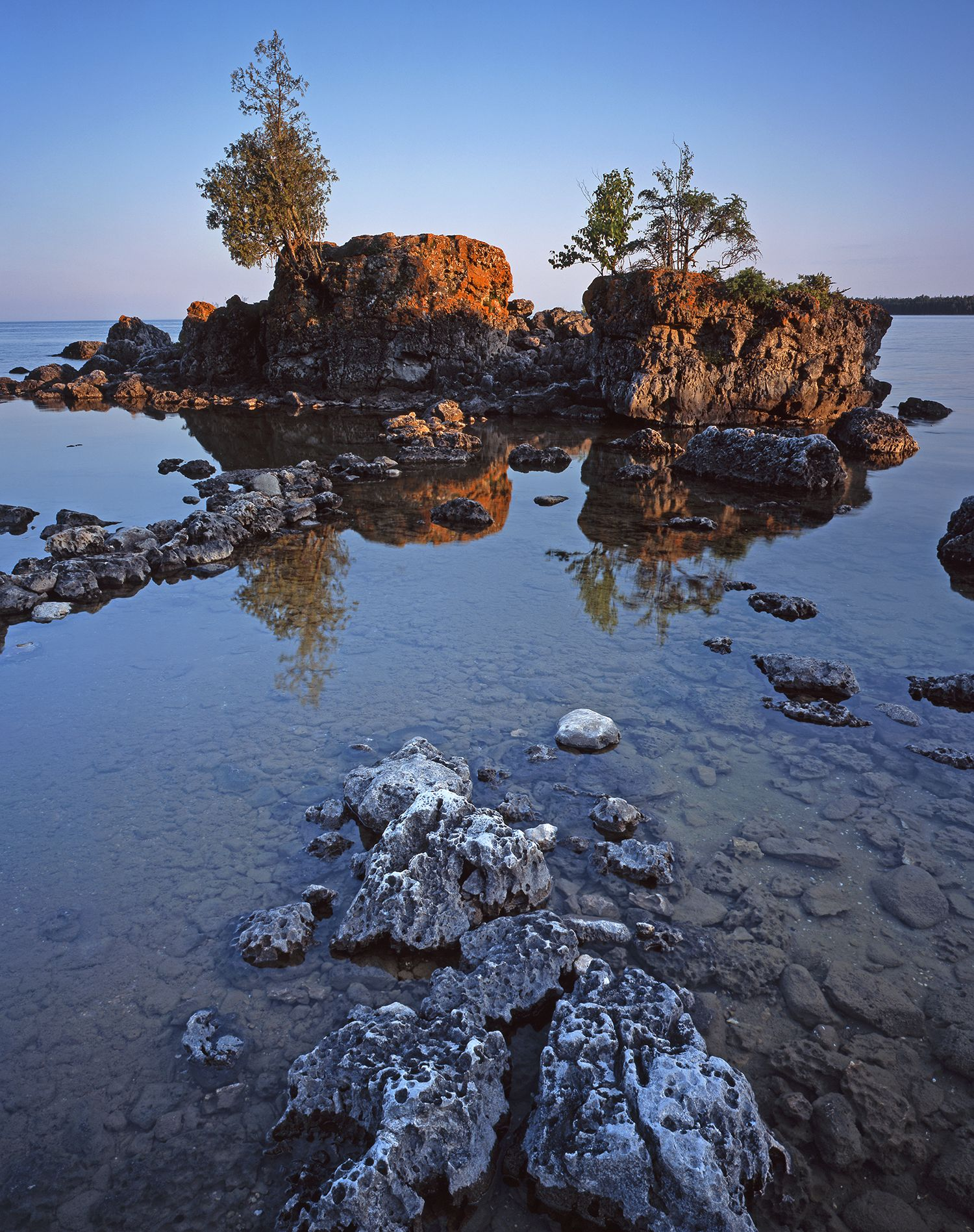 A rock formation on a calm shore.