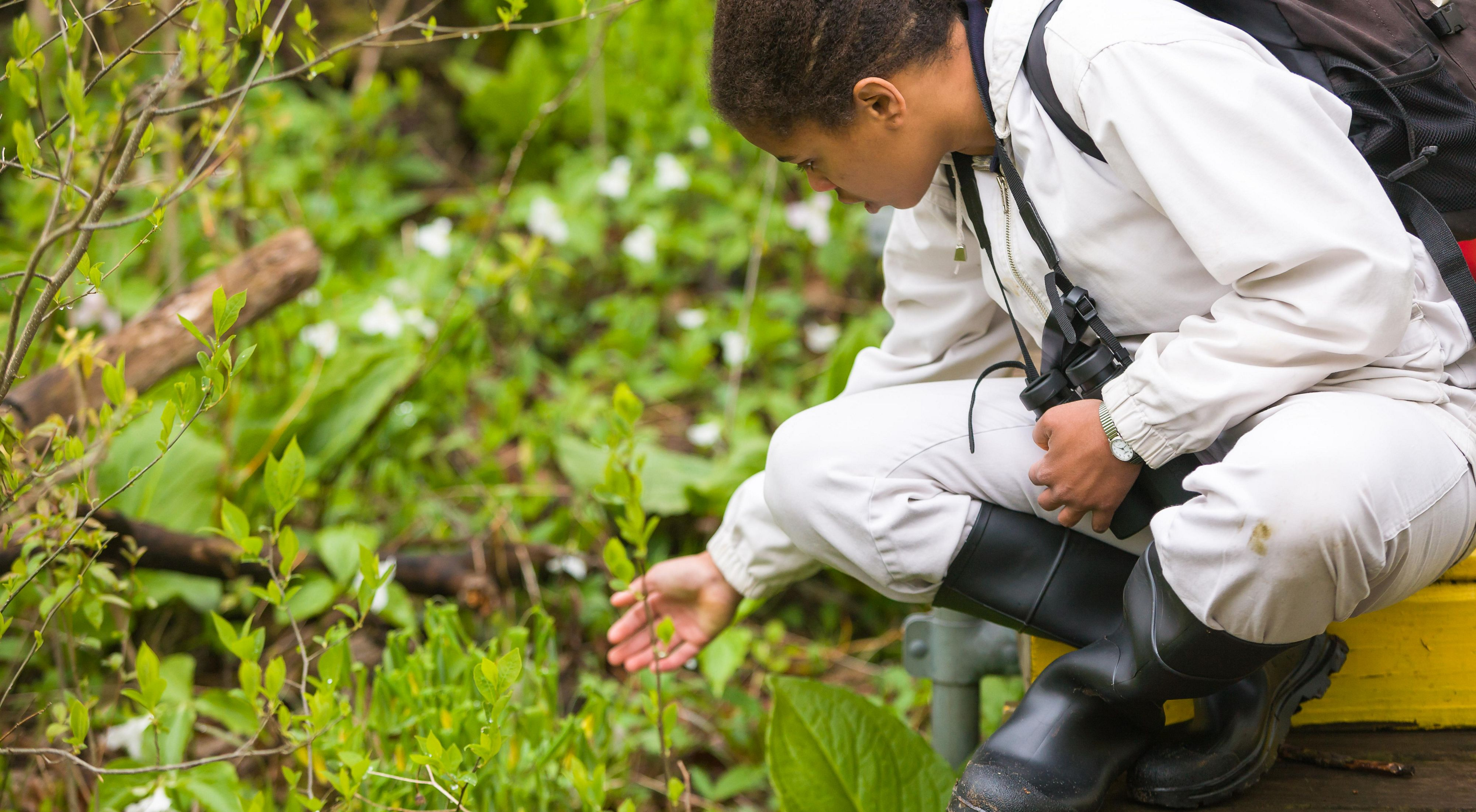 A girl wearing rubber boots and carrying binoculars bends over to look closely at a plant.