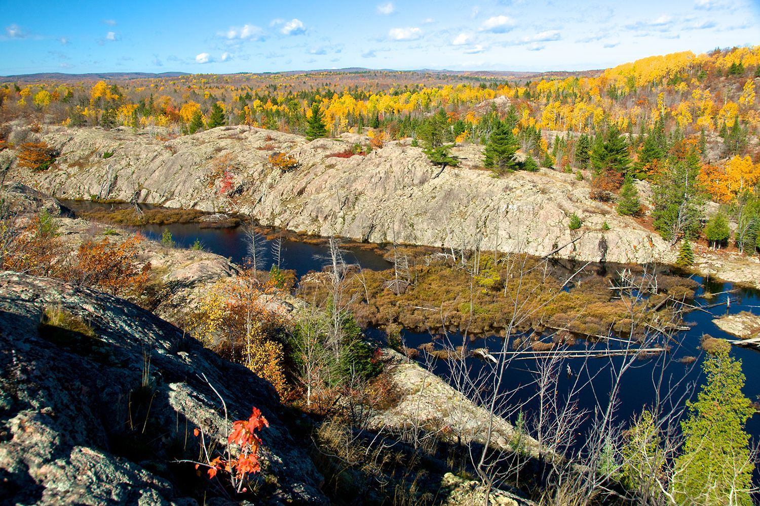 Rock formation along the side of a lake. Rolling forests changing color in the background.
