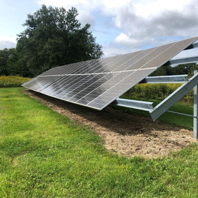 A solar array that has native plants surrounding the site but is mowed around and sprayed underneath the panels to prevent vegetation.