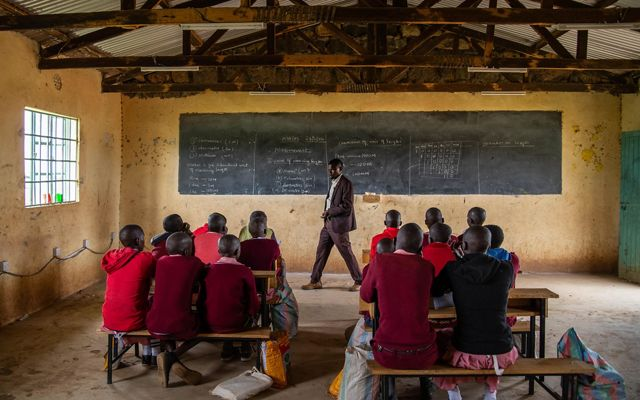 a man stands at the front of a classroom and a group of students in red clothing look up at him and a chalkboard