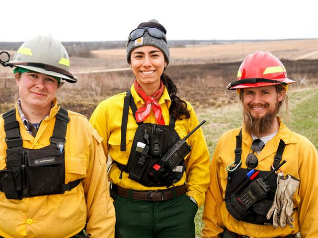 Three individuals wearing yellow fire suits stand in front of a recently burned field.