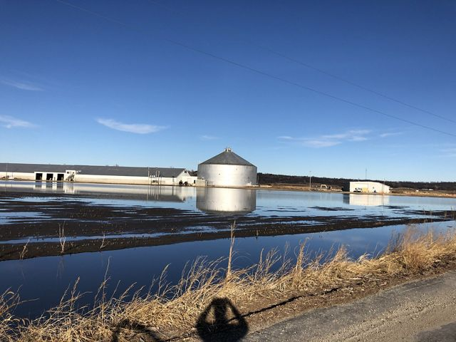 Flood waters covering farmland and buildings.