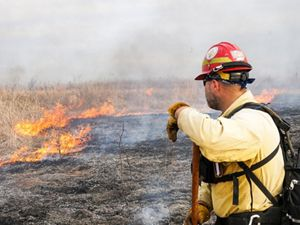 A man watches as a prairie field begins to burn during a prescribed burn.