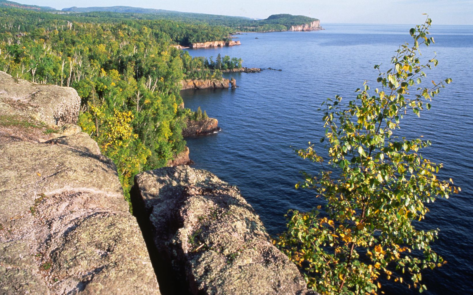 A green forest stretches along the shore of Lake Superior below a rocky outcrop.