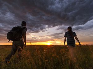 Hikers enjoy a hike in the prairie during the sweet light after a thunderstorm